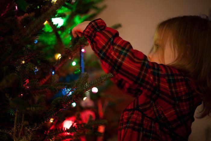 Niña adornando el árbol de Navidad