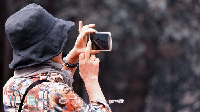 Turista haciendo fotos con su móvil
